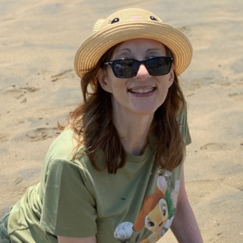 Paula at the beach in hat
