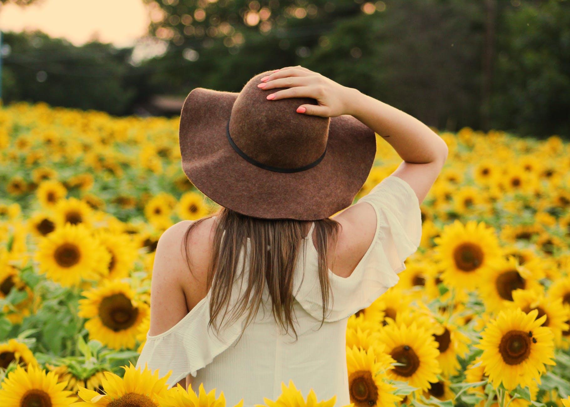 Woman hat sunflower field summer
