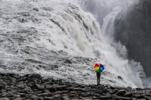Rainbow umbrella crashing waves